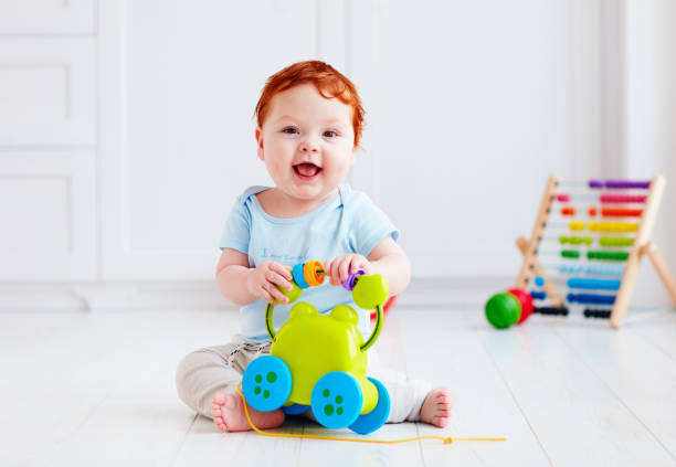 happy infant baby boy playing with toys at home stock photo