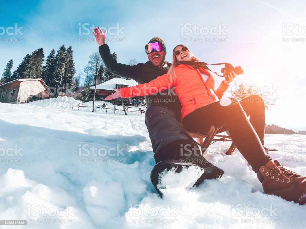 Glücklich Beeinflusser Paare, die Spaß mit Holz Vintage Rodeln auf Schnee hohe Berge - verrückte Jugendliche erhalten Winterurlaub - reisen und Urlaub-Konzept - Fokus auf Flächen – Foto