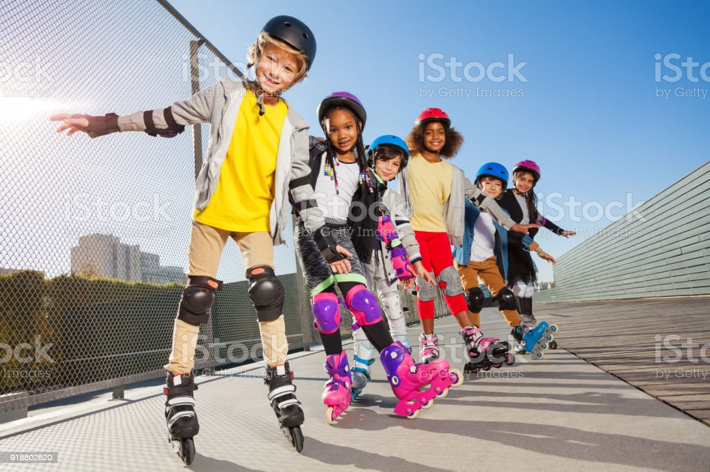 Happy in-line skaters standing one after another stock photo