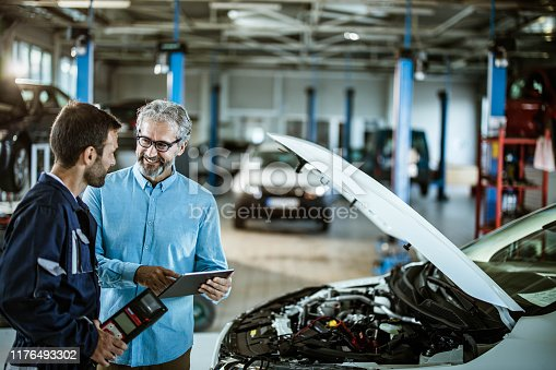 1137474295 istock photo Happy inspector using touchpad and talking to a mechanic in auto repair shop. 1176493302