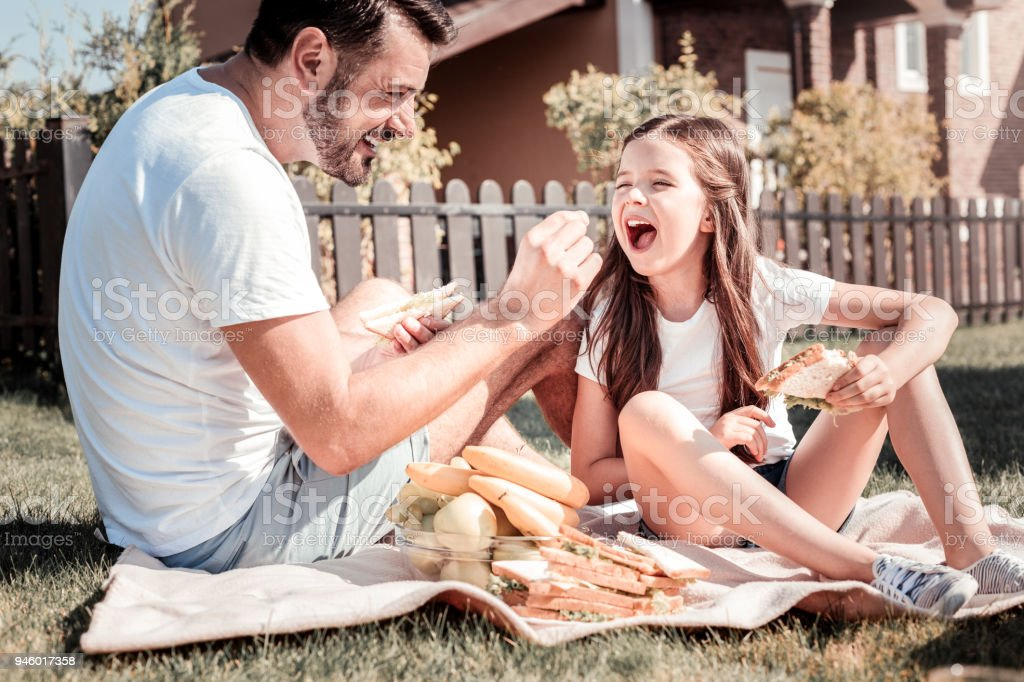 Happy interested father sitting and feeding his daughter. stock photo