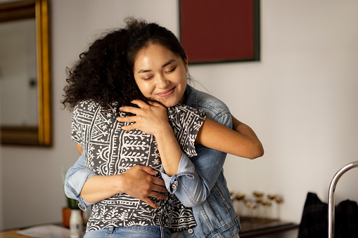 Young and happy woman of a Mongolian ethnicity hugging her African American female friend at home, smiling