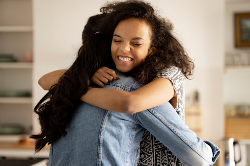 Young and happy African American woman hugging her female friend of a Mongolian ethnicity at home, smiling