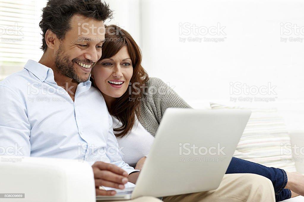 Happy interracial couple using laptop stock photo