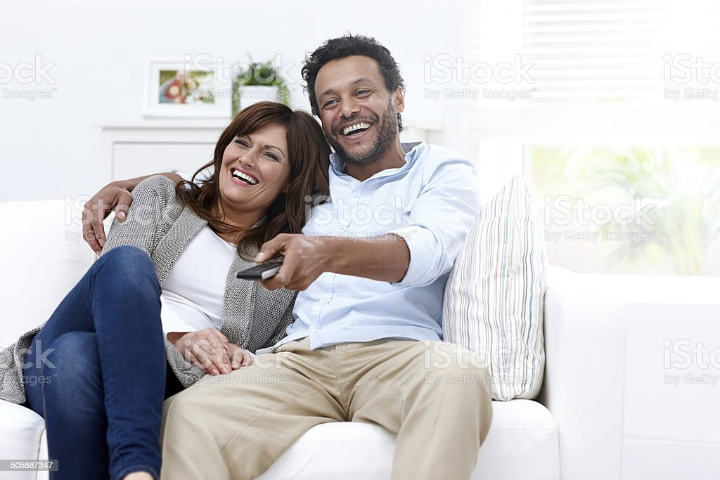 Happy interracial couple watching TV at home stock photo