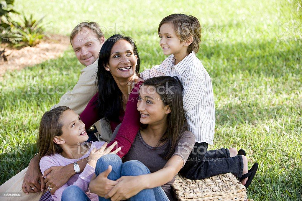 Happy interracial family of five enjoying a picnic at park royalty-free stock photo