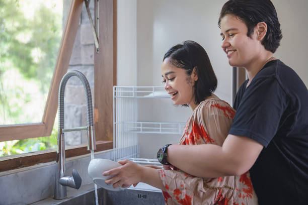 Happy interracial lesbian couple cleaning dishes together Shot of smiling Southeast Asian woman cleaning dishes while her girlfriend give a hug from behind cisgender stock pictures, royalty-free photos & images