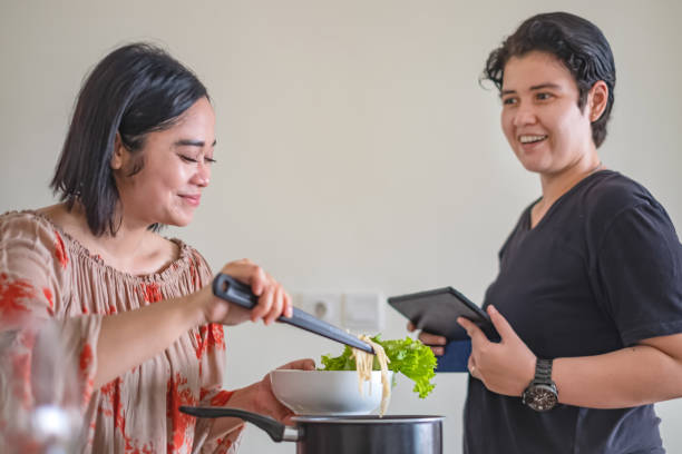 Happy interracial lesbian couple have fun cooking together Shot of happy interracial lesbian couple chatting while cooking healthy lunch meal together at home. cisgender stock pictures, royalty-free photos & images
