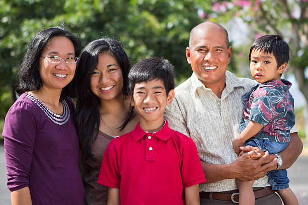 Happy Island Family This happy Filipino family, mother, daughter, father and sons, pose outside in a tropical, park like setting in sunny Hawaii. Families can be together forever. filipino ethnicity stock pictures, royalty-free photos & images