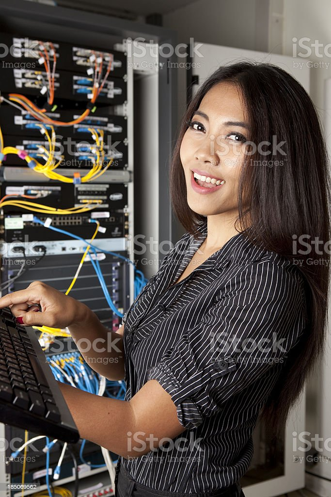 An attractive female IT worker in the server room.
