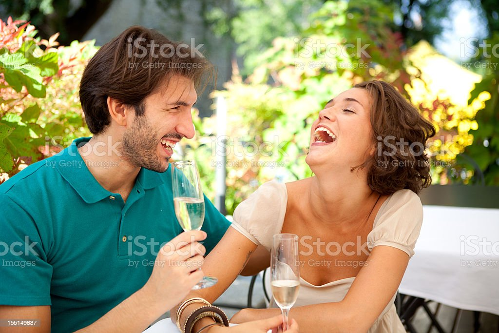 Happy Italian couple laughing in an outdoor restaurant stock photo