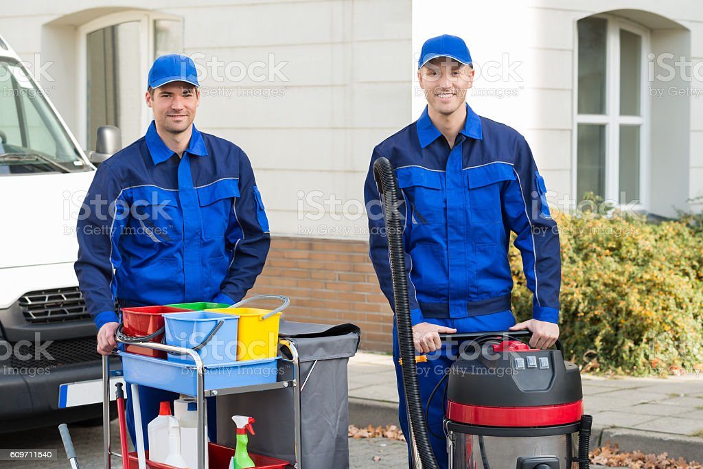 Happy Janitors Standing Against Truck stock photo