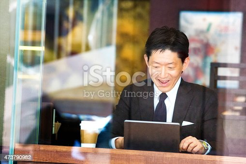 istock Happy Japanese businessman reads good news on tablet at cafe 473790982
