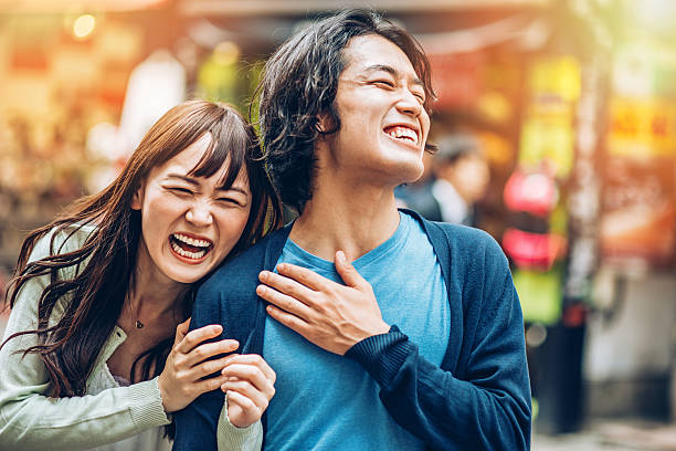 Happy Japanese couple Young Japanese couple smiling outdoors. Shot made during iStockalypse Tokyo 2015. japanese ethnicity stock pictures, royalty-free photos & images