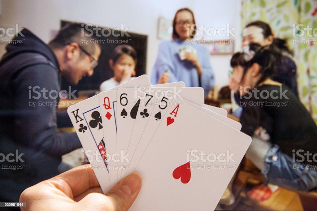 Happy Japanese family and friends playing cards stock photo