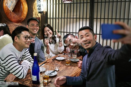 Group of smiling Japanese coworkers enjoying lively conversation, food, drinks, and selfie at a Tokyo restaurant.