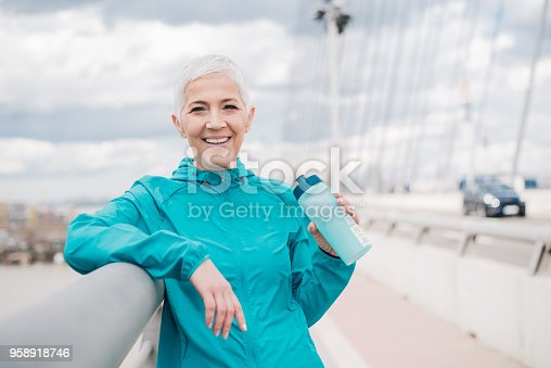 istock Happy jogger holding water bottle 958918746