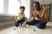 istock Happy joyful african dad and toddler son laughing playing together 1135353587