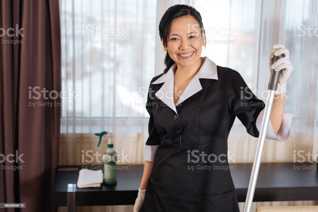Happy joyful chambermaid standing in the room Lizenzfreies stock-foto