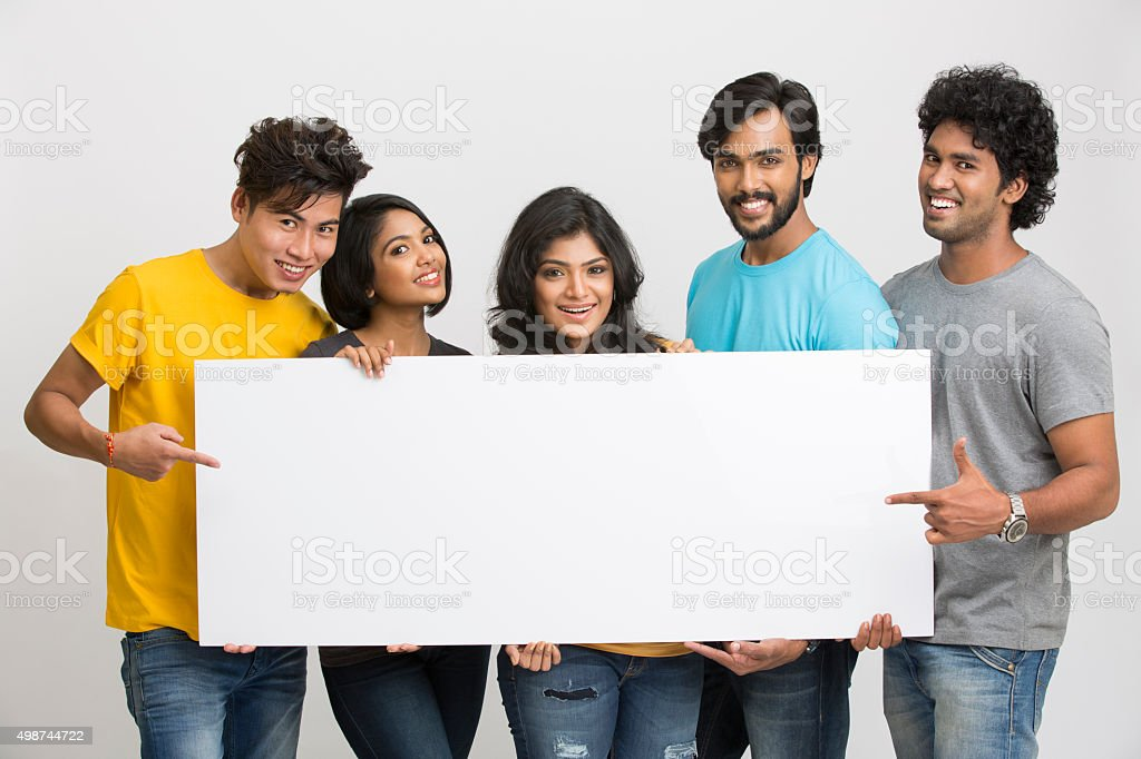 Happy joyful group of friends displaying white board stock photo
