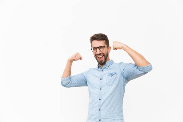 Happy joyful guy making hand winner gesture stock photo