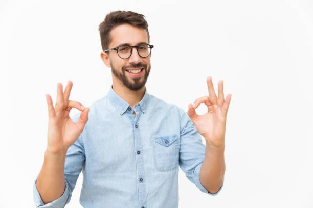 Happy joyful guy showing OK gesture stock photo