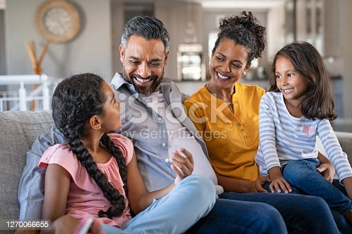 Cheerful multiethnic family at home sitting on sofa listening to daughter. Happy couple with two girls relaxing at home together. Smiling indian parents talking to their daughter at home in the living room.