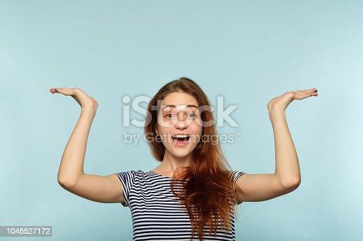istock happy joyful surprised girl point up above head 1045527172
