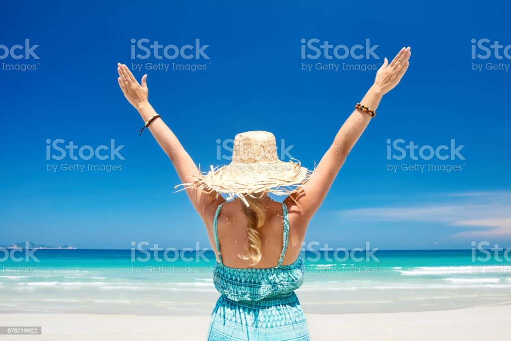 Happy joyful with arms up on tropical beach in summer during holidays travel. stock photo