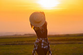 Happy joyful woman hiding under straw hat at meadow. Freedom and happiness concept.