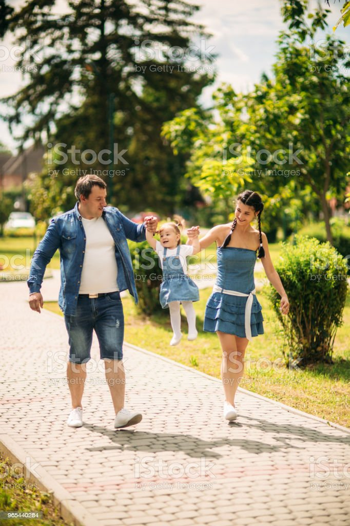 Happy joyful young family father, mother and little daughter having fun outdoors, playing together in summer park, countryside. Mom, Dad and kid laughing and hugging, enjoying nature outside royalty-free stock photo
