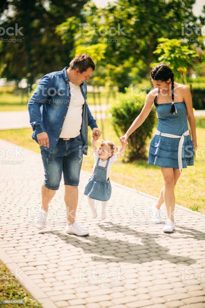 Pai de família jovem alegre feliz, mãe e filha se divertindo ao ar livre, jogando juntos no parque de verão, zona rural. Mãe, pai e filho rindo e abraçando, curtindo a natureza lá fora - Foto de stock de Adulto royalty-free