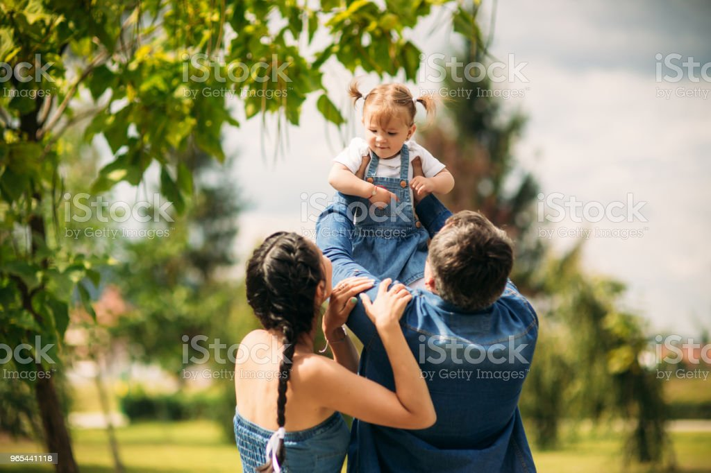 Happy joyful young family father, mother and little daughter having fun outdoors, playing together in summer park, countryside. Mom, Dad and kid laughing and hugging, enjoying nature outside zbiór zdjęć royalty-free