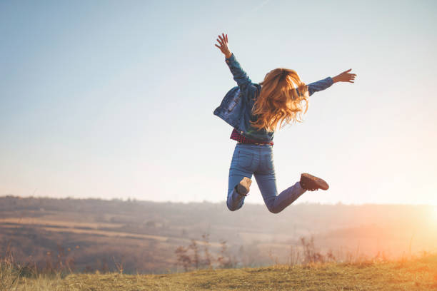 happy jump by girl in nature - alegria imagens e fotografias de stock