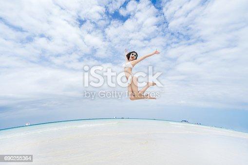 istock Happy jumping girl on the beach 690255364
