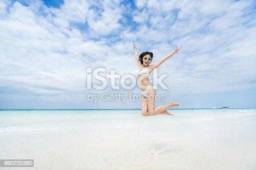 istock Happy jumping girl on the beach 690255380
