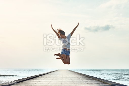 istock Happy jumping girl on the pier 605763240