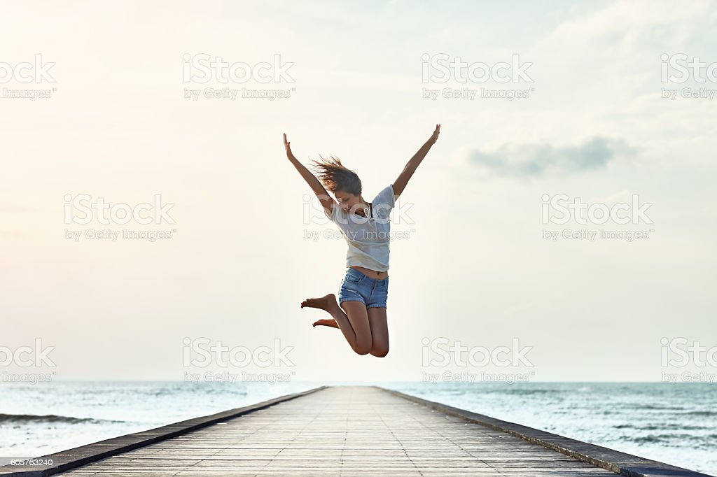 Happy jumping girl on the pier stock photo