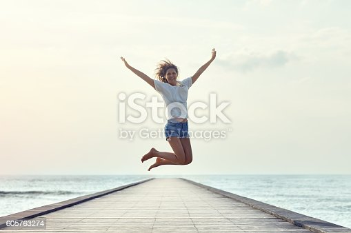 istock Happy jumping girl on the pier 605763274