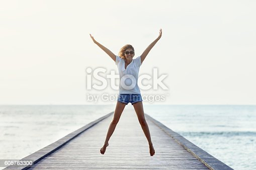 istock Happy jumping girl on the pier 605763300