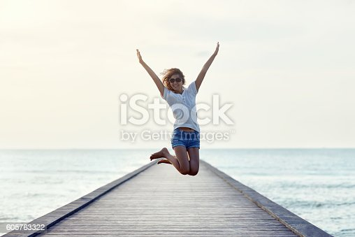istock Happy jumping girl on the pier 605763322