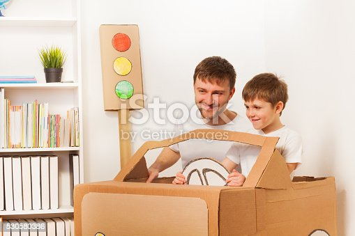 942256562istockphoto Happy kid and his dad driving toy cardboard car 530580386