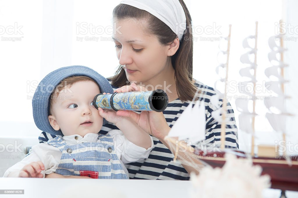 Happy kid and mom playing with toy sailing boat indoors. stock photo