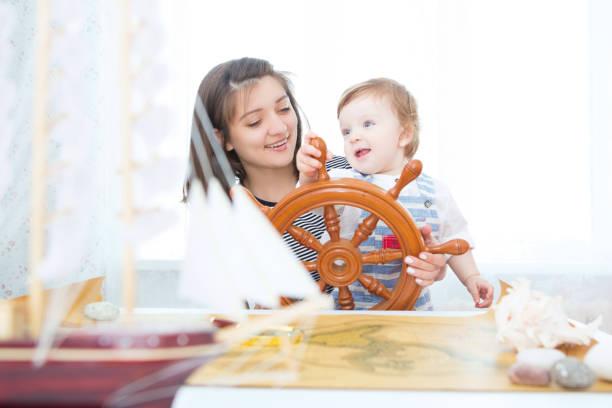 glückliches kind und mutter spielen mit spielzeug-segelboot im innenbereich. - küstenfamilienzimmer stock-fotos und bilder