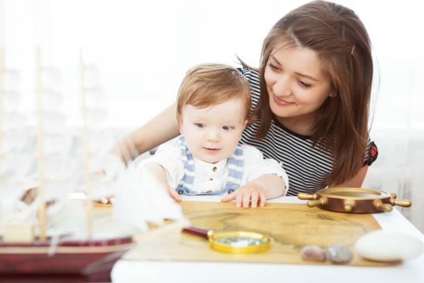 glückliches kind und mama spielt mit spielzeug segelboot drinnen. reisen und abenteuer-konzept - küstenfamilienzimmer stock-fotos und bilder