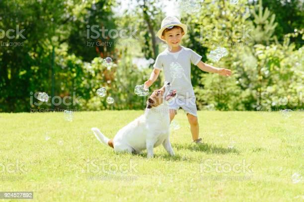 Happy kid and pet dog playing witn soap bubbles at backyard lawn picture id924527892?b=1&k=6&m=924527892&s=612x612&h=z9zoc4yk5knwnzgic ij53h9erxevuowwdwbafvbn6k=