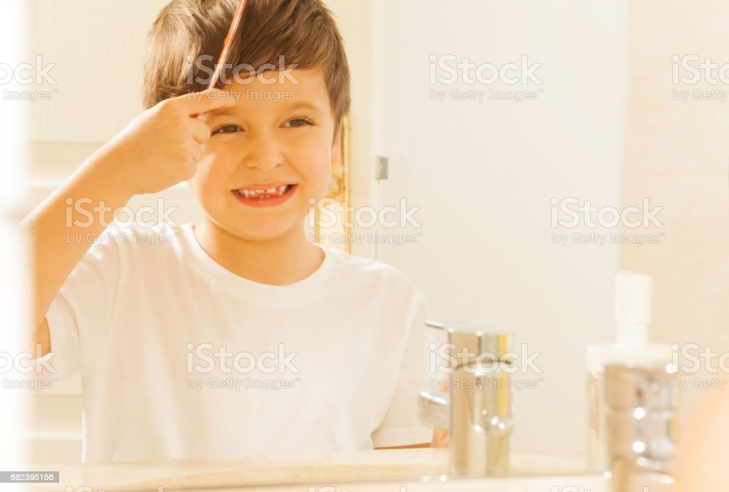 Happy kid boy combing his hair in the morning royalty-free stock photo