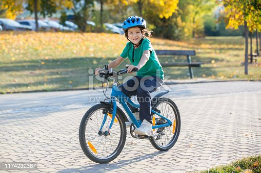 Happy kid boy, having fun in autumn park with a bicycle on beautiful fall day. Active child wearing bike helmet