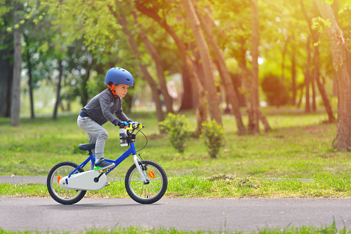 Happy kid boy of 5 years having fun in spring park with a bicycle on beautiful fall day. Active child wearing bike helmet