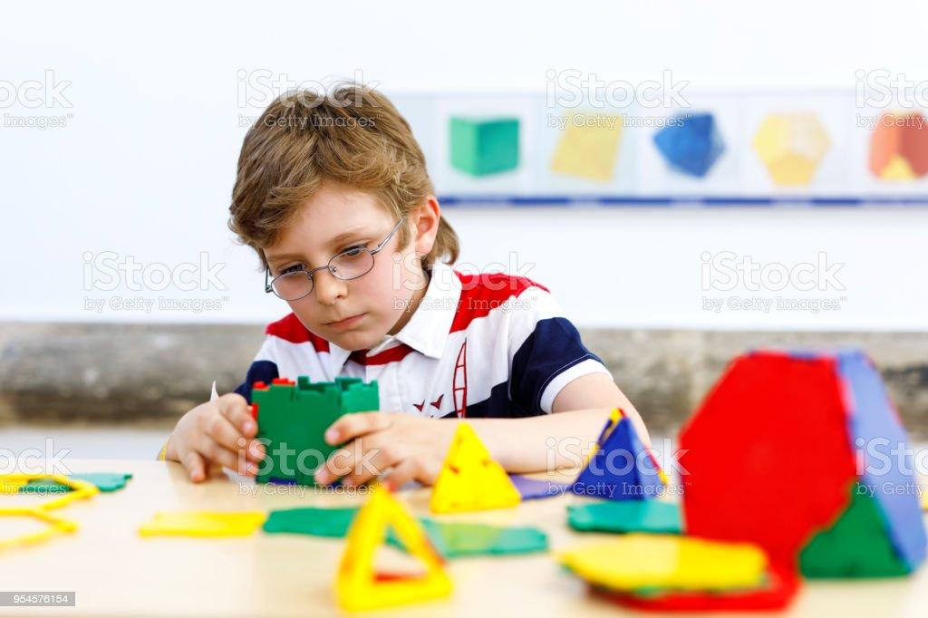 4e10a4c40c06ec Jongen van de gelukkige jongen met bril met plezier met bouwen en maken van  geometrische figuren